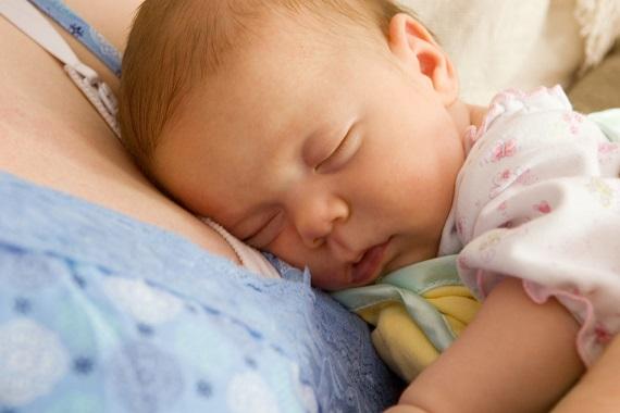 Bebelusa ce doarme pe pieptul mamei