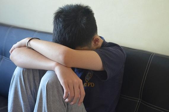Baietel trist, care sta pe canapea