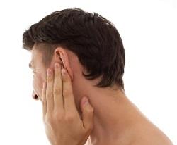 Barbat care isi duce mana la ureche din cauza disconfortului resimtit