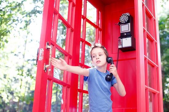 Baietel ce incearca sa vorbeasca intr-o cabina telefonica