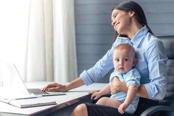 Mama ce vorbeste la telefon si lucreaza cu bebelusul in brate