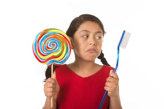 Fetita ce tine intr-o mana o acadea uriasa si in cealalta o periuta de dinti