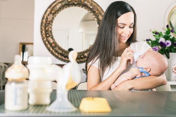 Mama ce sta pe un scaun și ii da bebelusului lapte cu biberonul