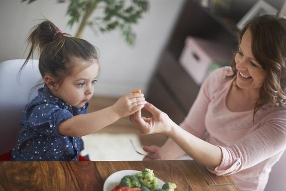 Mama ce ii ofera fetitei sale o bucatica de morcov