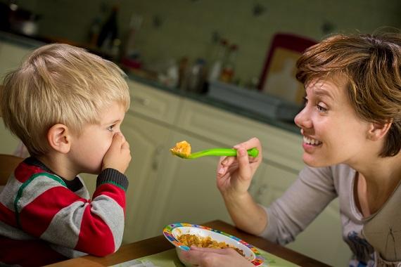 Mama ce incearca sa-i dea sa manance baietelului ei, care isi acopera gura