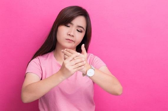 Femeie ce isi scoate greu inelul din cauza faptului ca are degetele umflate