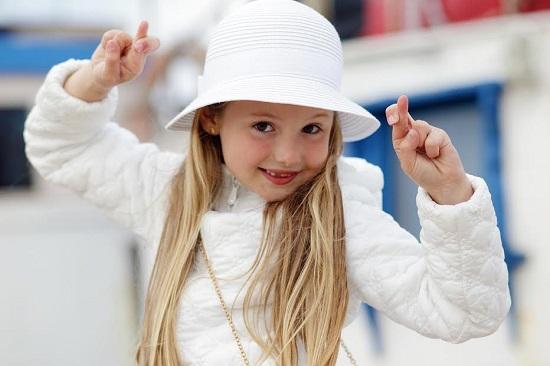 Fetita ce incearca sa simbolizeze cu degetele ideea de noroc