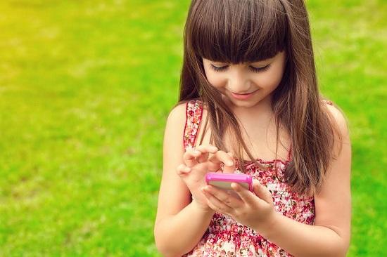 Fetita ce manuieste un telefon mobil