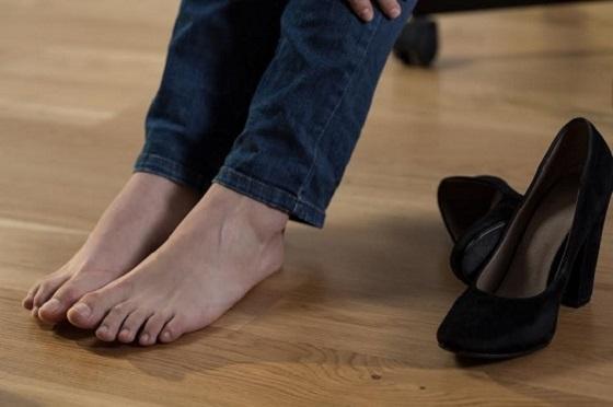 Femeie ce si-a scos pantofii din cauza picioarelor umflate