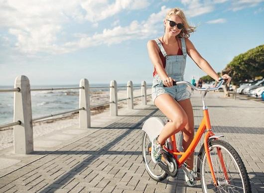 Tanara ce se plimba cu bicicleta pe faleza