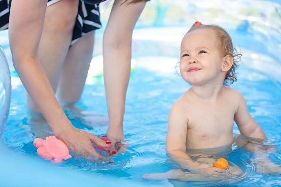 Mama ce se joaca cu bebelusul din piscina gonflabila
