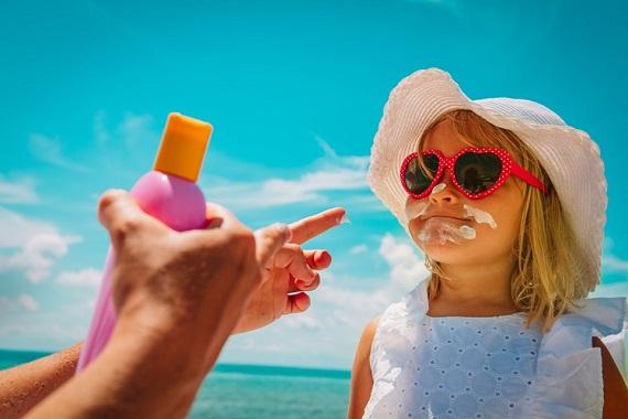 Femeie care o da pe o fetita cu crema de protectie solara