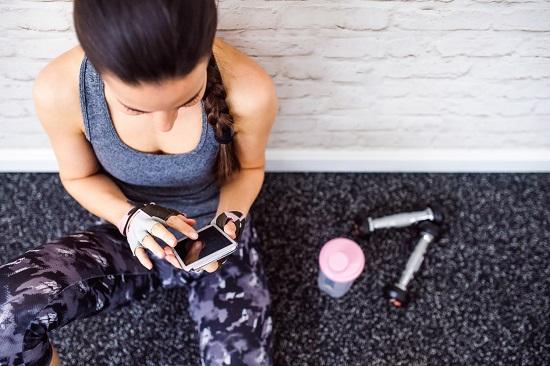 Fata ce sta pe jos, in sala de sport, dand mesaje pe telefon