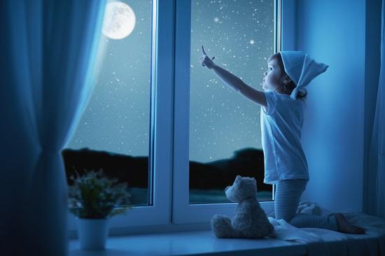 Fetita gata de culcare, ce arata cu degetul spre cer