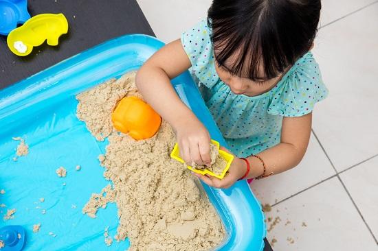 Fetita ce umple o forma de plastic cu nisip kinetic