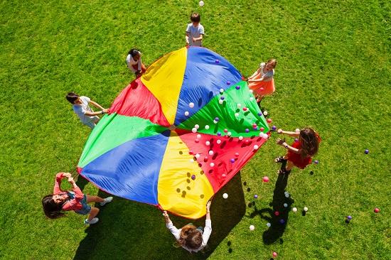 Copii ce se joaca cu bile colorate, pe o panza ca de parasuta