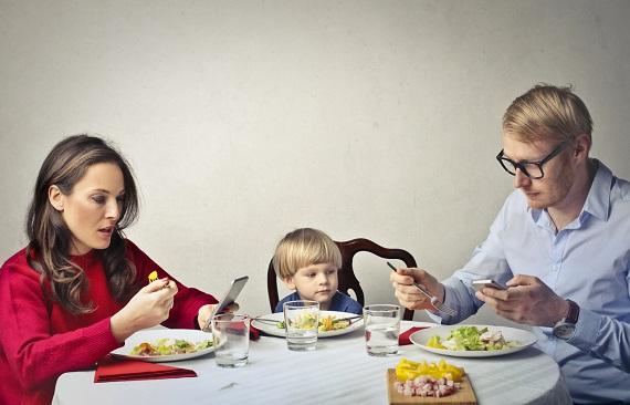 Familie la masa, mama si tatal stand cu ochii in telefon
