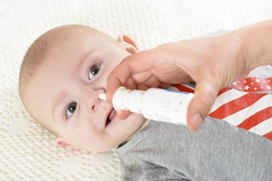Mama ce-i pune bebelusului picaturi de nas