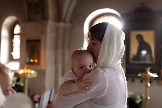 Fetita in bratele mamei sale, in biserica