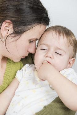 Mama ce isi tine in brate bebelusul aproape adormit