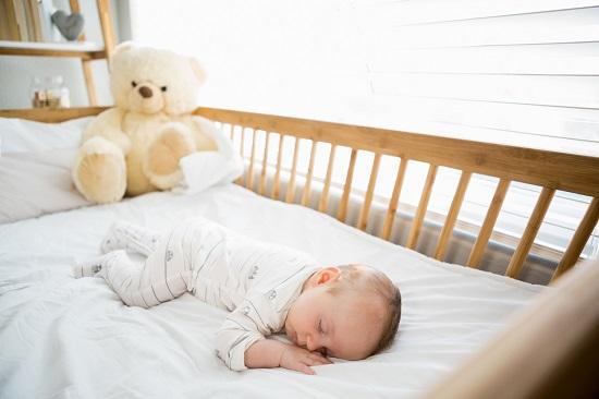 Bebelus ce doarme in patut
