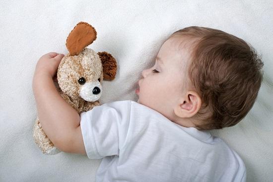 Bebelus ce doarme cu o jucarie
