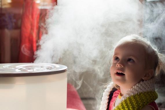 Fetita ce sta in fata unei oale cu apa fierbinte pentru a inhala aburi