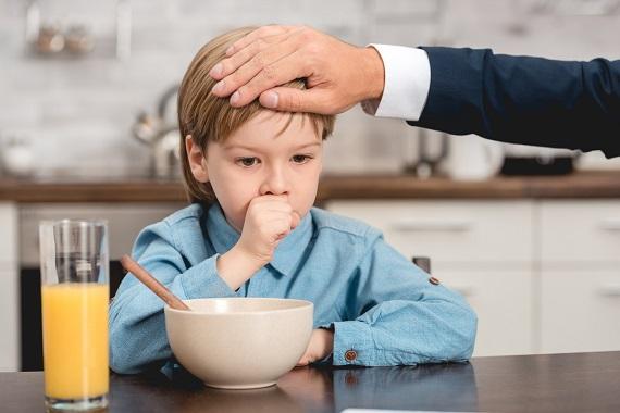 Tata ce pune mana pe fruntea baietelului sau pentru a vedea daca nu cumva are febra
