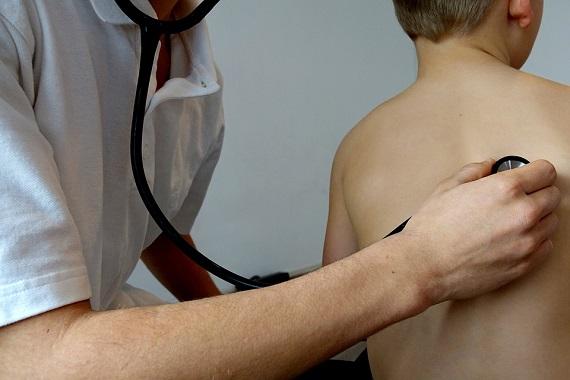 Medicul asculta cu stetoscopul un baietel