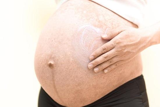 Femeie insarcinata ce se unge pe abdomen cu un unguent