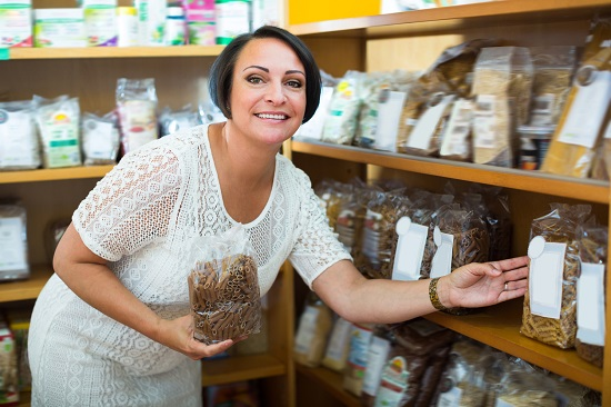 Femeie la magazin, tinand in mana o punga cu paste din cereale integrale