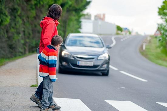 Mama ce se uita daca vine vreo masina, astfel incat sa poata  traversa in siguranta cu copilul ei
