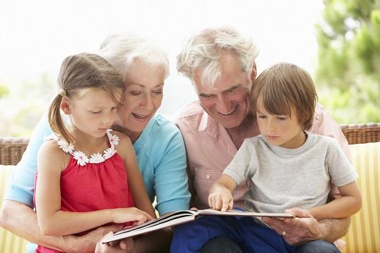 Bunici alaturi de nepotii lor, uitandu-se impreuna pe o carte