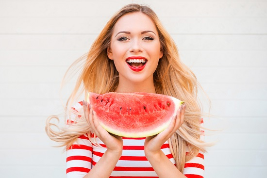Fata vesela, cu o felie de pepene rosu in mana