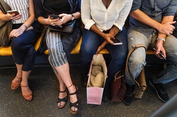 3 femei si un barbat care umbla pe smartphone