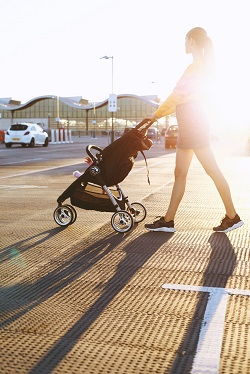 Femeie ce isi plimba bebelusul in carucior