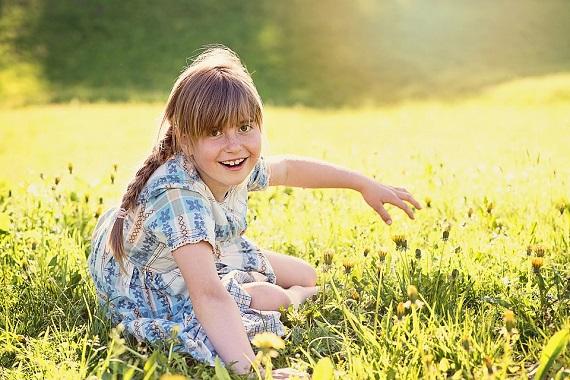 Fetita care sta la soare, pe iarba