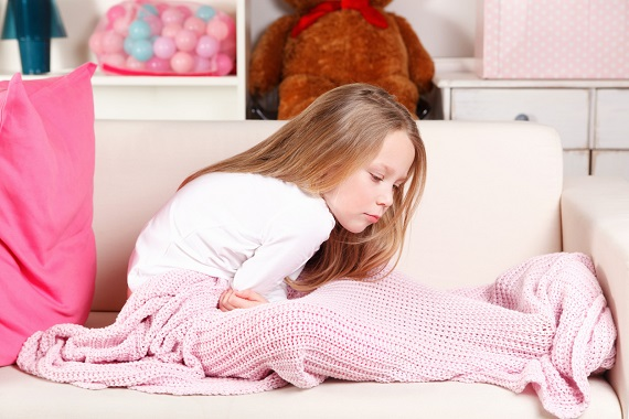 Fetita cu dureri abdominale, care sta pe canapea