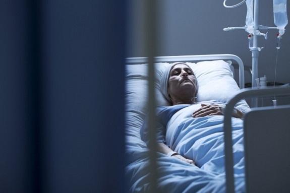 Femeie aflata pe spatul de spital, cu perfuzie