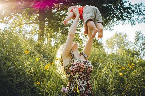Mama care isi ridica bebelusul in brate pentru a-l expune la soare