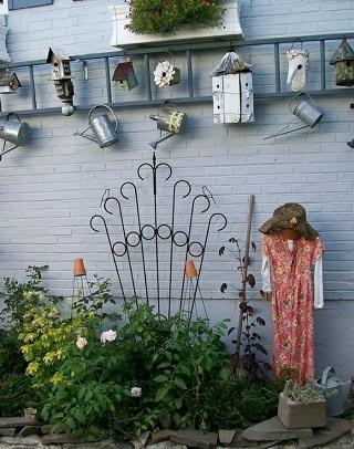 Gard de gradina decorat cu stropitori din aluminiu si cu casute de pasari