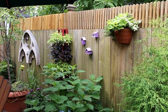 Gard decorat cu ghivece cu flori si cu casute pentru pasarele
