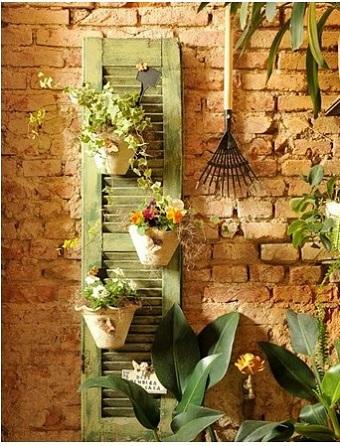 Gard de gradina decorat cu o grebla, cu ghivece si plante