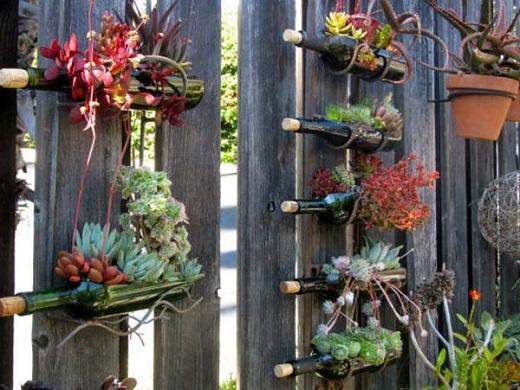 Gard din gradina decorat cu sticle-suport pentru flori