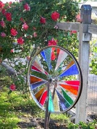 Gard de gradina decorat cu o roata de bicicleta colorata si cu trandafiri
