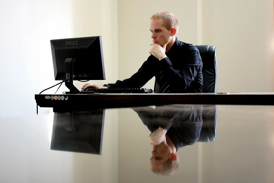 Barbat la birou, in fata computerului