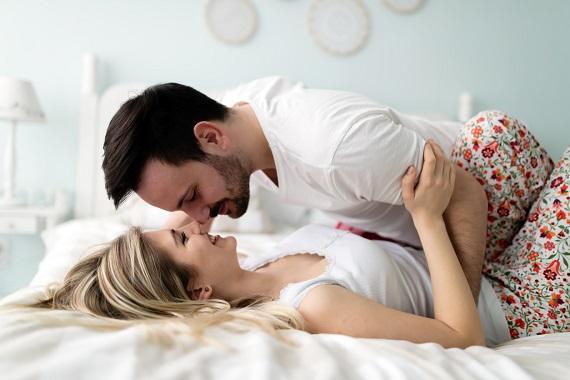 Cuplu pe pat, sarutandu-se