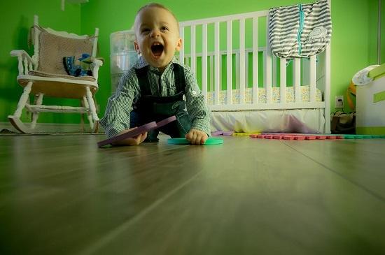 Bebelus ce se joaca pe jos