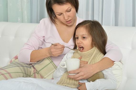 Mama ce sta alaturi de fetita bolnava pentru ca aceasta sa bea ceai