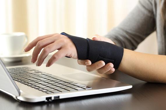 Femeie ce poarta o orteza cand lucreaza la calculator